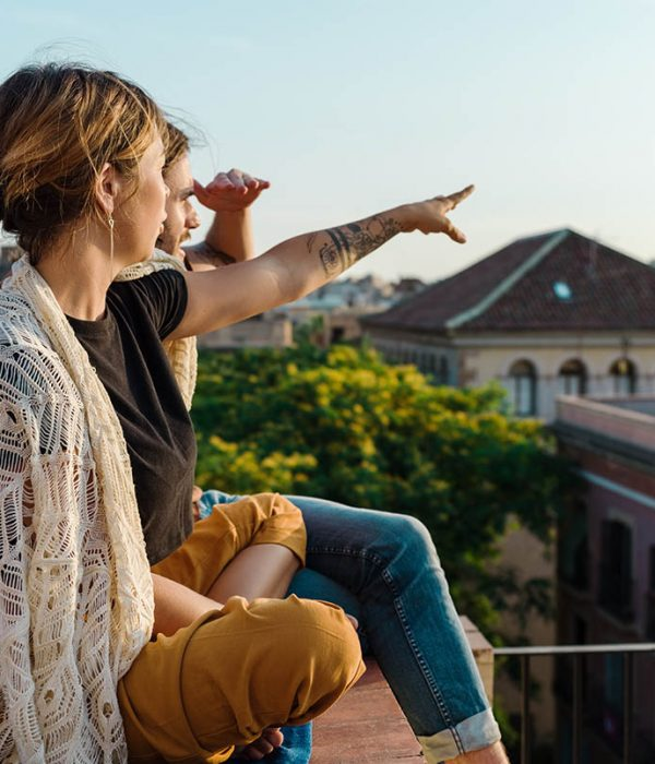 Side view of woman sitting with man on rooftop pointing away and observing city in sunlight